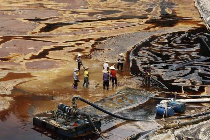 Workers drain away polluted water near the Zijin copper mine in Shanghang on July 13, 2010, after pollution from the mine contaminated the Ting River, a major waterway in southeast China's Fujian Province. Water pollution is a severe environmental problem in China and contributes to high cancer rates. (STR/AFP/Getty Images)